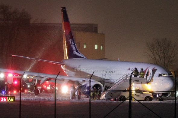 Authorities investigate the scene of a Delta Air Lines Boeing 737-800 jet that slid off a runway in the snow after arriving at Dane County Regional Airport in Madison, Wis., Monday, Dec. 16, 2013. No one was hurt. (AP Photo/Wisconsin State Journal, M.P. King)