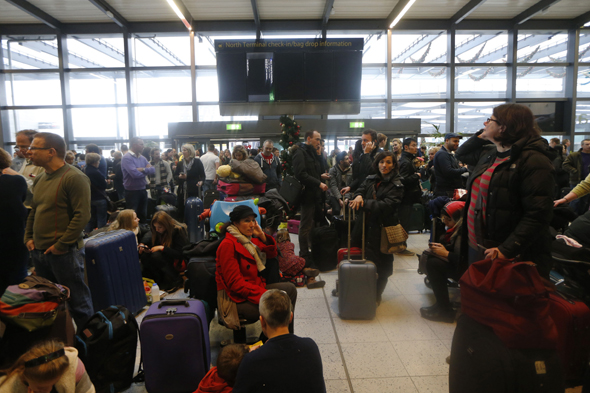 Passengers wait underneath blank departure screens following a power outage at the North Terminal of London Gatwick Airport in Horley, England, Tuesday, Dec. 24, 2013. A severe winter storm has caused major travel problems in Britain, leading to substantial delays Tuesday at London Gatwick Airport and on roads and rail lines at the height of the Christmas travel period. (AP Photo/Sang Tan)