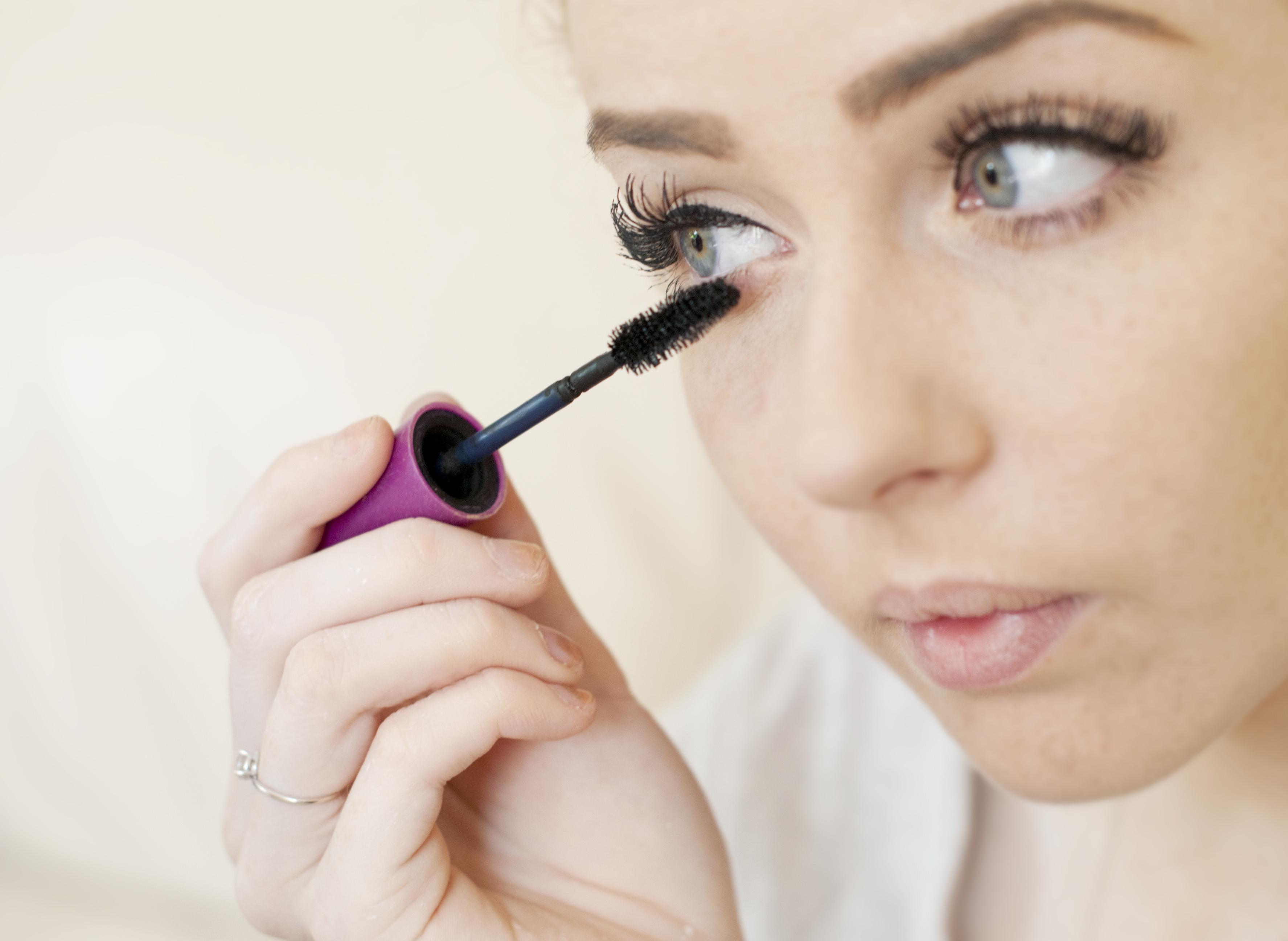 Young european woman applying mascara make-up to her eyelashes