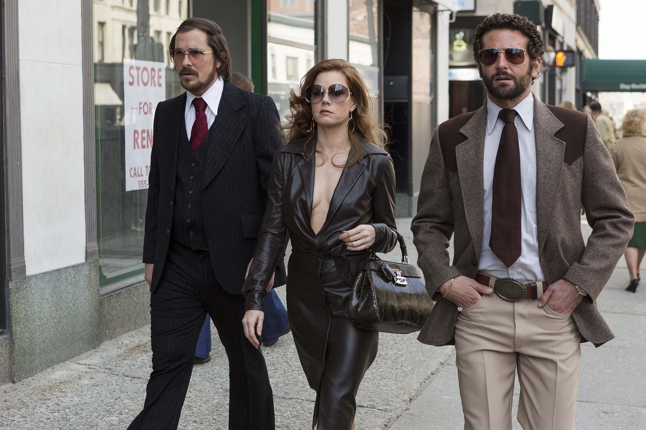 Irving Rosenfeld (Christian Bale), Sydney Prosser (Amy Adams) & Richie Dimaso (Bradley Cooper) walk down Lexington Ave. in Columbia Pictures' AMERICAN HUSTLE.  (Christian Bale suit, tie, shirt, glasses: vintage / Amy Adams dress: Halston, glasses: vintage Christian Dior, bag: Gucci, shoes: vintage / Bradley Cooper suit, tie shirt, belt, glasses: vintage)