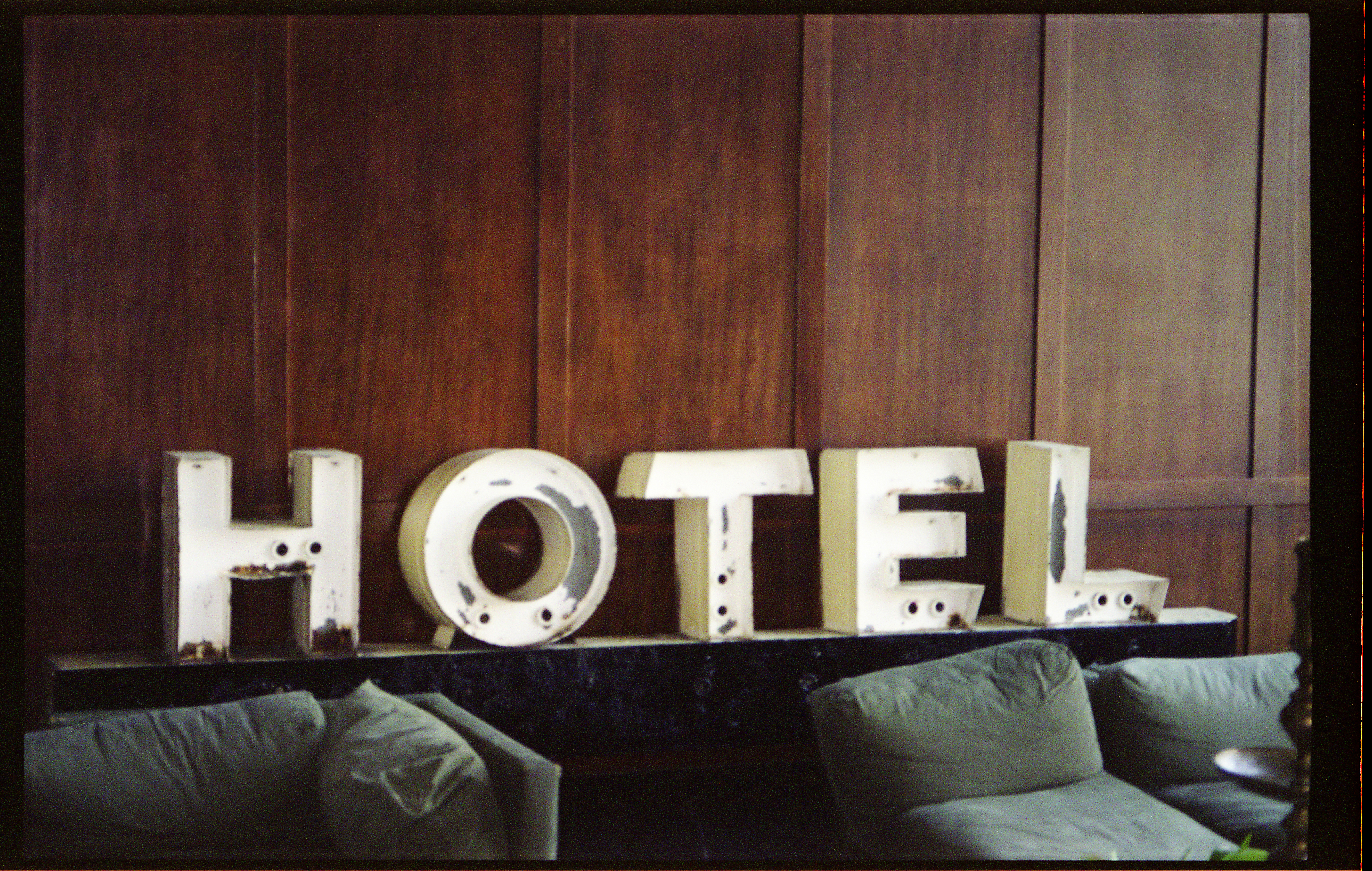 Vintage white 'HOTEL' sign leaning against dark wooden wall in lobby of ACE Hotel in Portland, Oregon.