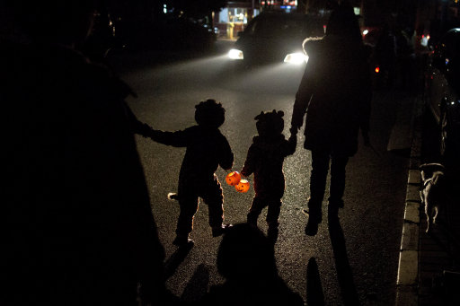 Two children dressed in their Halloween costumes hold pumpkin-shaped lanterns while walking on their way to ask for candies from neighbors the night before Halloween in Beijing, China, Wednesday, Oct. 30, 2013. (AP Photo/Alexander F. Yuan)