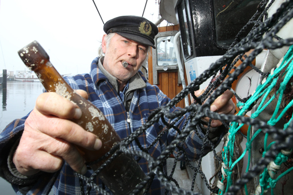 Fisher Konrad Fischer holds a message in a bottle from 1913 on the fishing cutter
