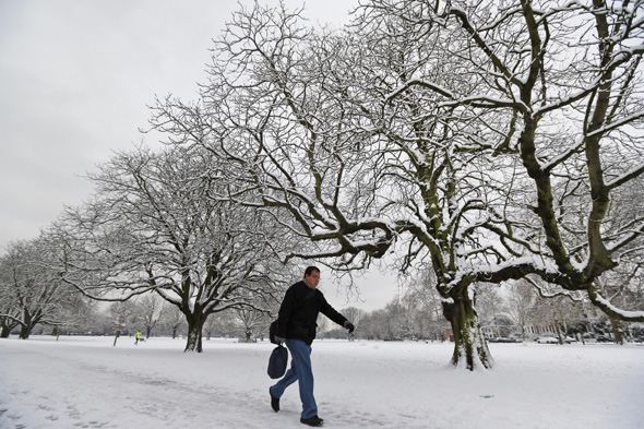 A man walks in a park, covered by snow in west London, Monday, Jan. 21, 2013. The big freeze across Britain is here to stay, with more heavy snow and falling temperatures forecast for Britain and Scotland. (AP Photo/Lefteris Pitarakis)