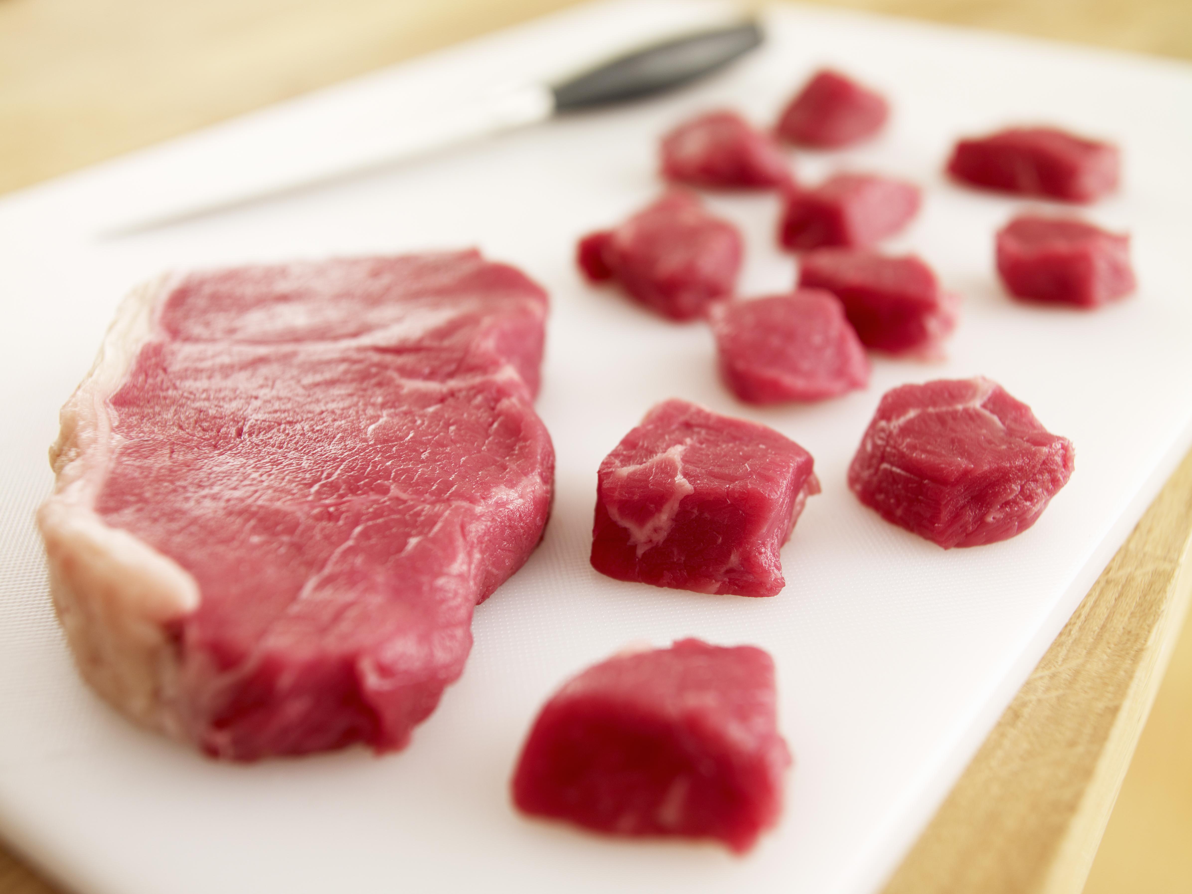 Cubed raw steak on cutting board