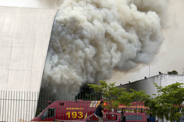 Smoke pours out of the Simon Bolivar auditorium at the Latin America Memorial in Sao Paulo, Brazil, Friday, Nov. 29, 2013. The fire department of Brazil's biggest city says a fire swept through the large auditorium that is part of the political, cultural and leisure complex designed by famed architect Oscar Niemeyer. No casualties were reported. Two firefighters had to be treated for smoke inhalation. (AP Photo/Andre Penner)