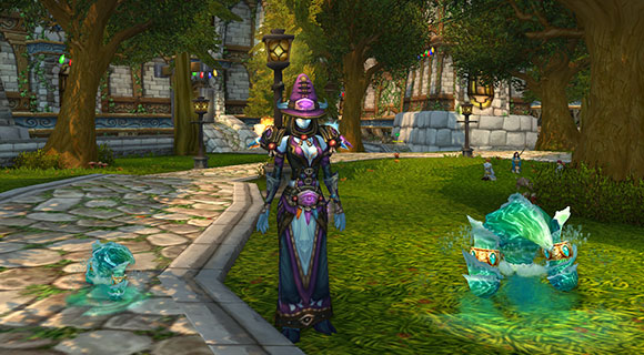 A draenei mage stands with two water elementals, one is very small and the other is a bit bigger.