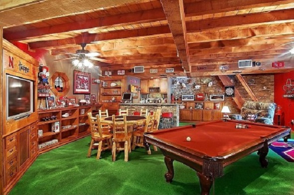 Man cave with a bar, pool table, sports memorabilia and green turf for carpet.