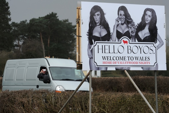 ***EXCLUSIVE - FREE FOR USE***  ABERGAVENNY, UNITED KINGDOM - FEBRUARY 23: A van driver takes a picture of an MTV pop-up billboard depicting The Valley TV Reality Stars Natalee Harris, Lateysha Grace and Jenna Jonathan on February 23, 2014 in Abergavenny, Wales.  A CHEEKY alternative ëWelcome to Walesí sign on the A465 Welsh border has been setting male commuterís hearts racing. The pop-up billboard, which was installed on Sunday morning (Feb 23), carries the phrase 'Hello Boyos' - a cheeky nod to the iconic Wonderbra ads of the mid 90s. Erected by MTV bosses to celebrate the third season of reality TV show The Valleys, which hits TV screens on Tuesday night at 10pm on MTV, the eye-popping sign features three of the showís biggest stars Natalee Harris, Lateysha Grace and Jenna Jonathan in racy underwear.  The striking design is being trialled on the A465 on the Welsh border, but is due to be rolled out at several crossings into Wales later this week in advance of the new series airing.  PHOTOGRAPH BY Dan Rowley / Barcroft Media  UK Office, London. T +44 845 370 2233 W www.barcroftmedia.com  USA Office, New York City. T +1 212 796 2458 W www.barcroftusa.com  Indian Office, Delhi. T +91 11 4053 2429 W www.barcroftindia.com