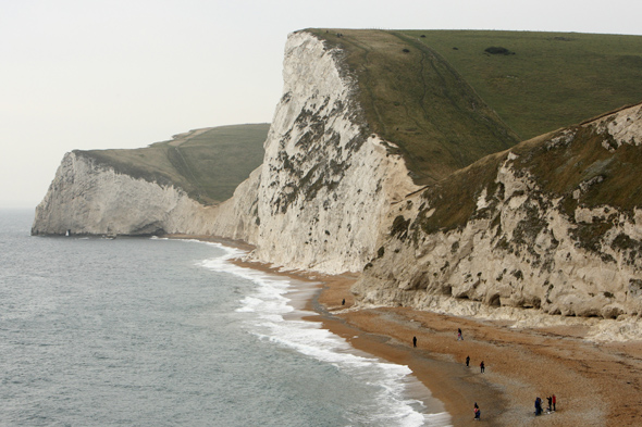 A view of the beach and cliffs at Durdle Door on Dorset's Jurassic Coast.  The half term school holiday and news of a recent significant find of the jaw bones of a pliosaur brought hunters out in their droves. The local coast is classified as a World Heritage Site and is famous for its abundance of fossils. It covers 95 miles of coastline in East Devon and Dorset, with rocks recording 185 million years of the Earth's history. World Heritage status was achieved because of the site's unique insight into the earth sciences as it clearly depicts a geological ?walk through time' spanning the Triassic, Jurassic and Cretaceous periods. Rain causes landslides allowing the cliff face to reveal the treasures beneath.