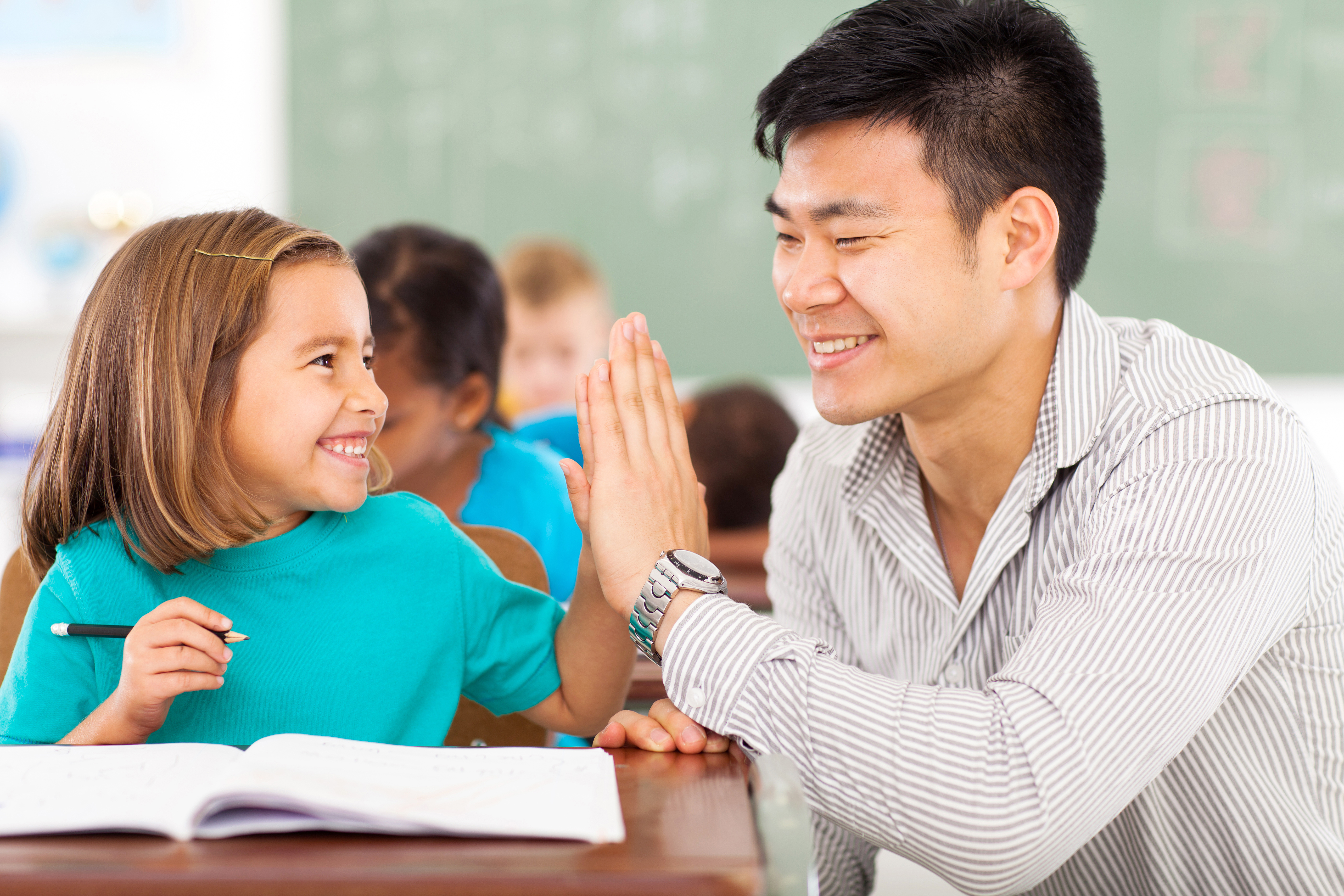 cheerful elementary school teacher and student high five in classroom