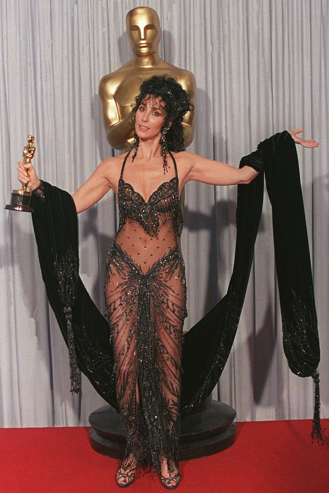 Cher shows off her Oscar for best actress and her Bob Mackie black sequined see-through gown after winning the award for her role in