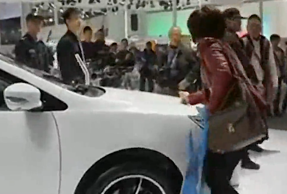 woman scratches car at motor show