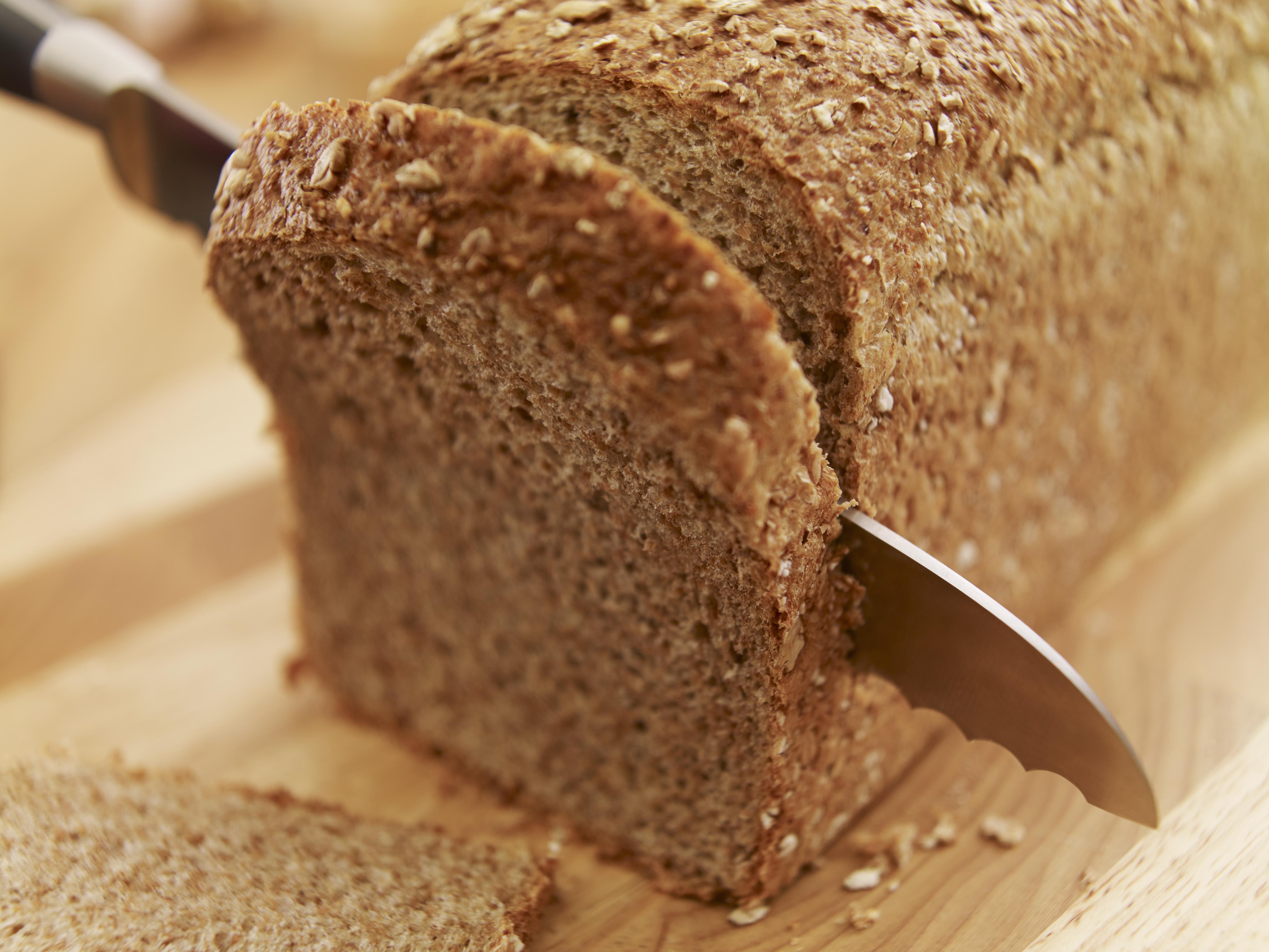 Knife slicing fresh bread loaf