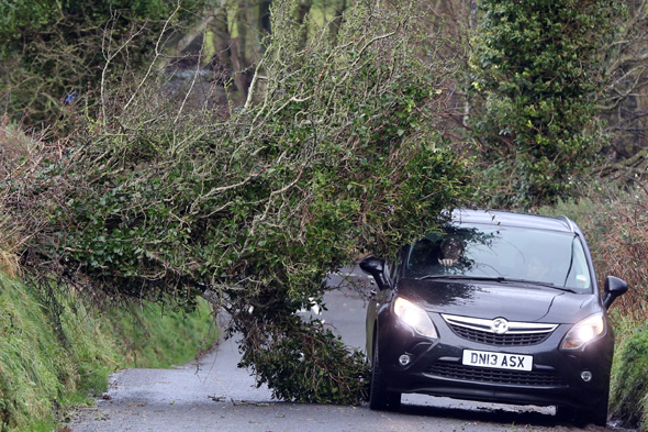 A motorist navigates past a fallen tree in north Antrim as power companies have been condemned for failing to restore supplies to thousands of households as the UK suffered a second major storm over the Christmas holiday.