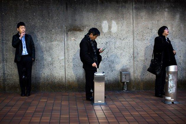 Des hommes fument des cigarettes dans une zone désignée dans le quartier Naka-Meguro de