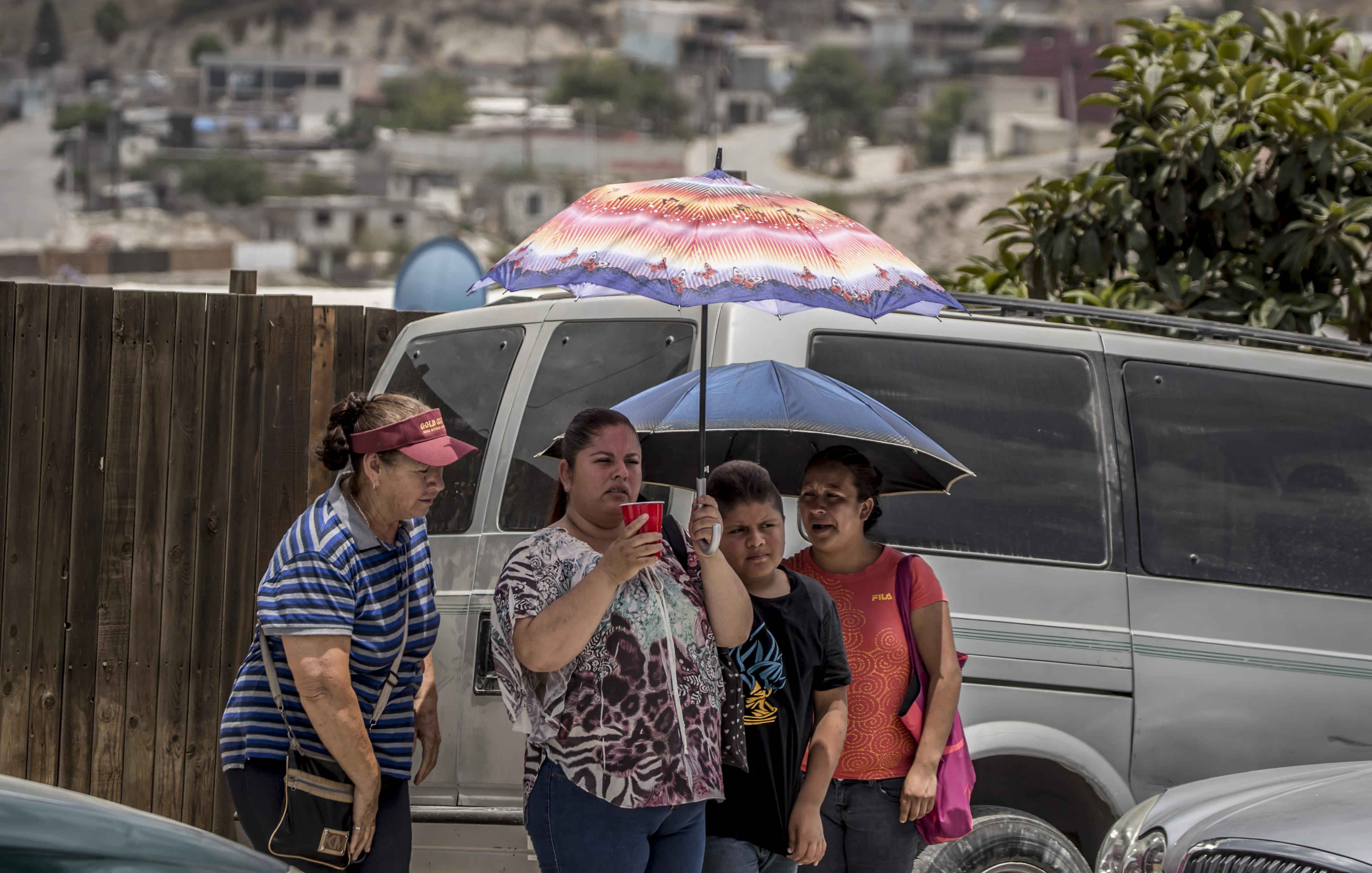 Mujeres en Tijuana usan sombrillas para protegerse del intenso