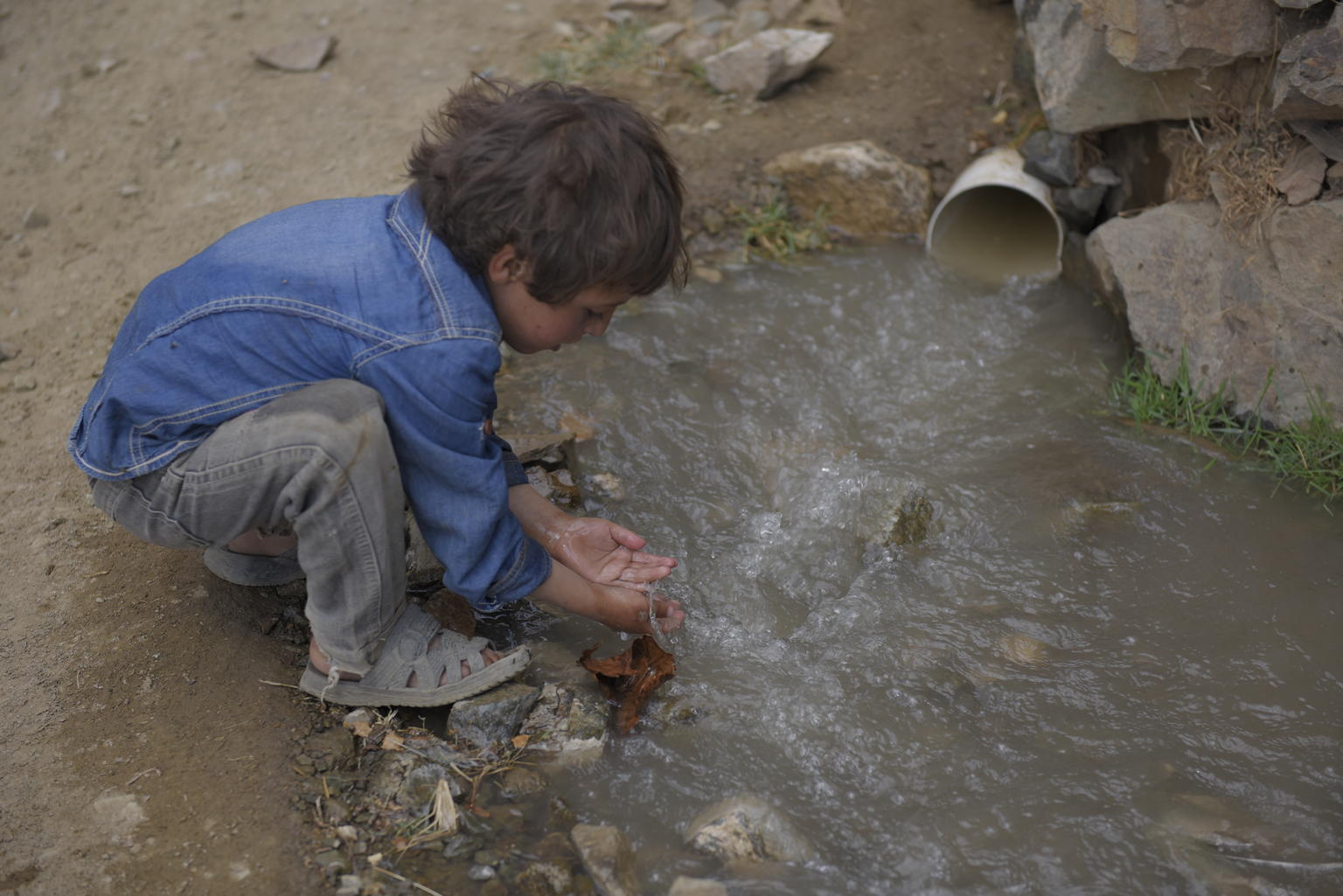 Le mardi 24 octobre 2017 : Un enfant se lave les mains dans l'eau non traitée provenant d'un tuyau d'égout...