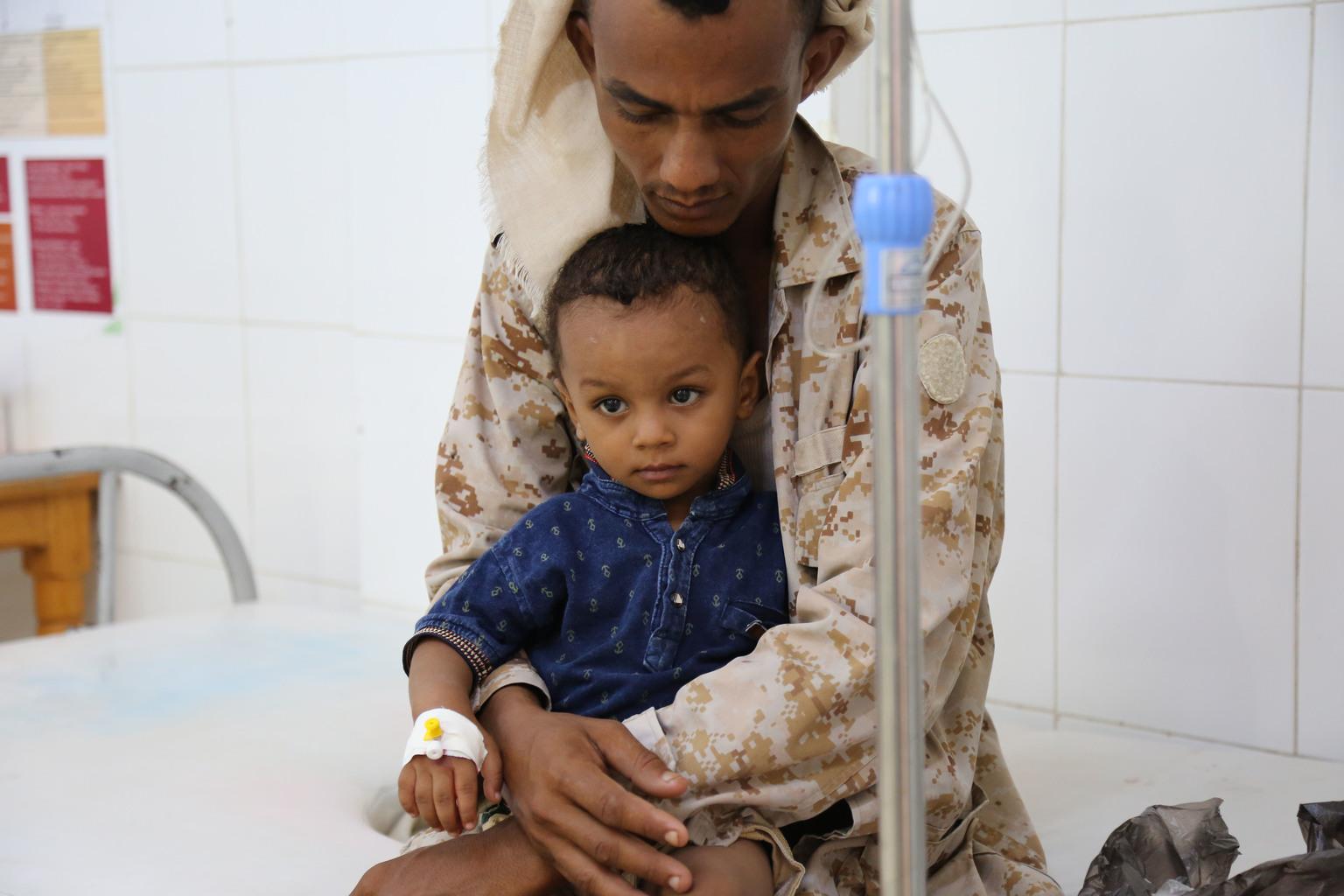 Le lundi 14 août 2017 : Un père tient son enfant souffrant du choléra alors que le petit reçoit un traitement...