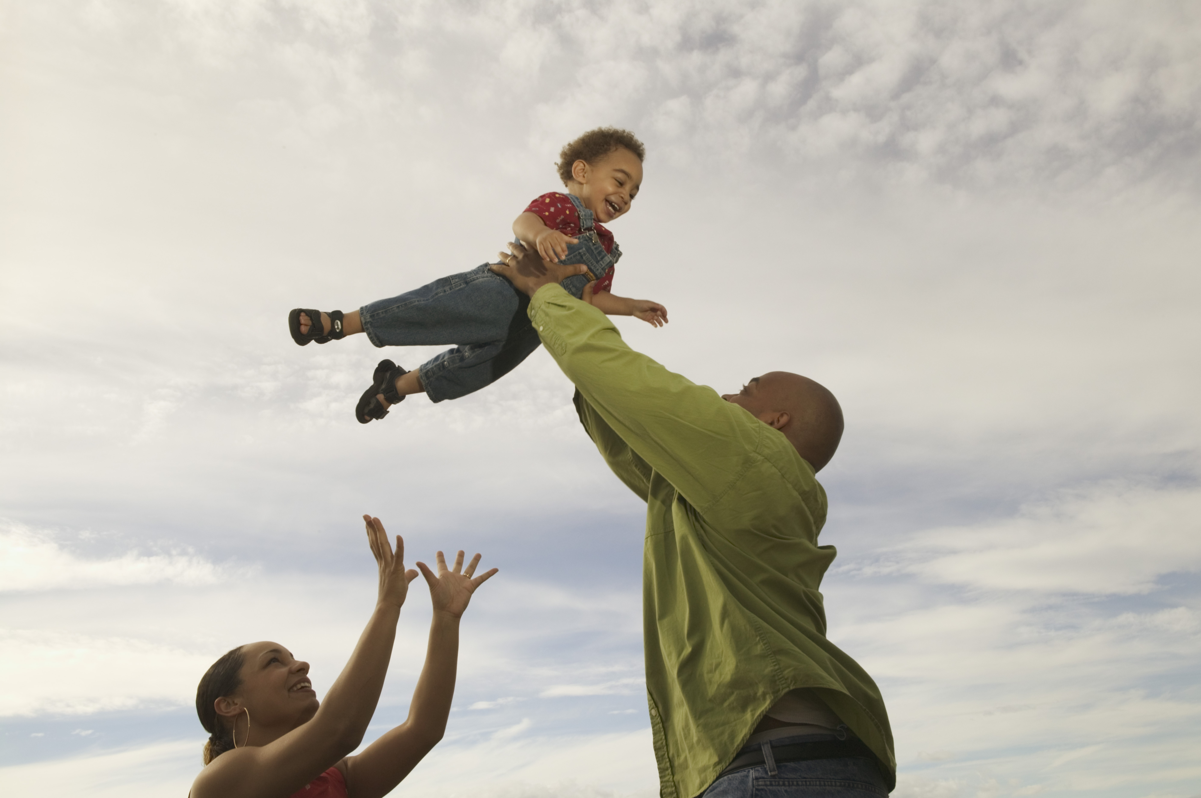 African-American father lifts his son into a cloudy white sky, with mother close by