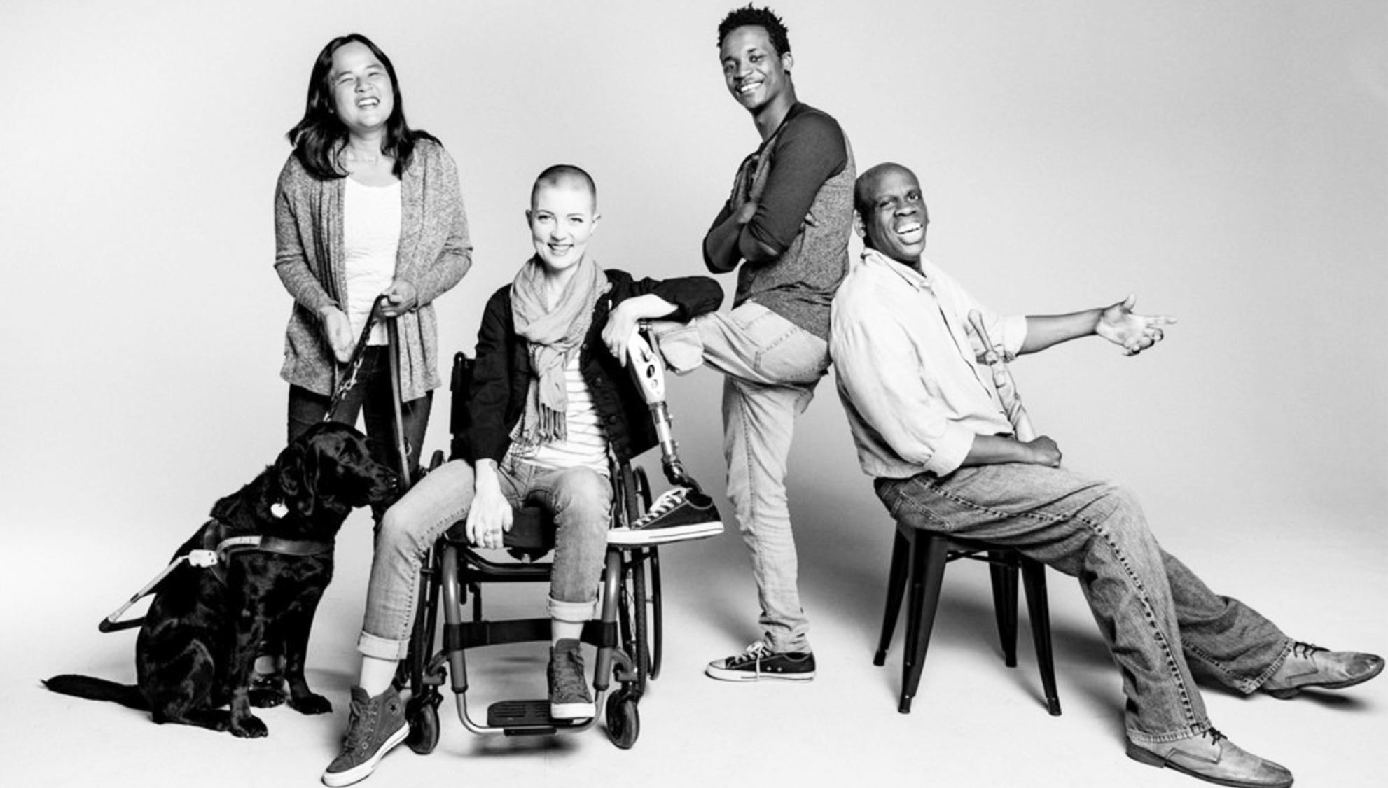 Black and white picture of diverse group of four people, one with a guide dog, one in a wheelchair, smiling and proud.