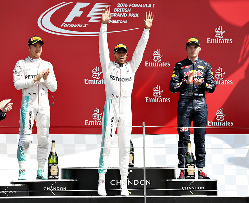 Lewis Hamilton of Great Britain and Mercedes GP celebrates his win on the podium with Nico Rosberg of Germany and Mercedes GP and Max Verstappen of Netherlands and Red Bull Racing during the Formula One Grand Prix of Great Britain at Silverstone on July 10, 2016 in Northampton, England.