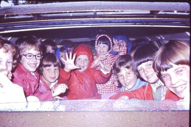 Heidi est au centre dans le manteau rouge à capuche. Sa petite soeur est à côté d'elle avec le manteau...