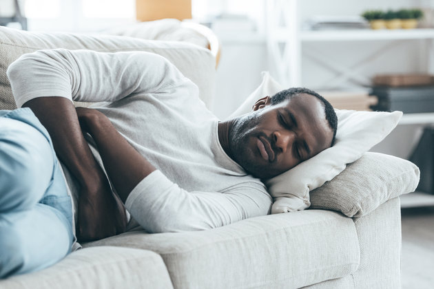 Handsome young African man keeping eyes closed while lying on the sofa and touching his