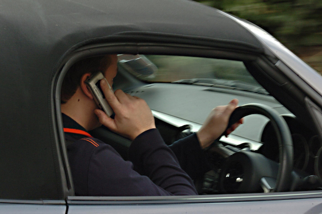 Embargoed to 0001 Friday November 25 POSED BY MODEL Undated file photo of a man using his mobile phone while driving, as a new study suggests that fewer than three in five (59\%) people would ask a driver to stop using a hand-held mobile phone if they were a passenger in the car.
