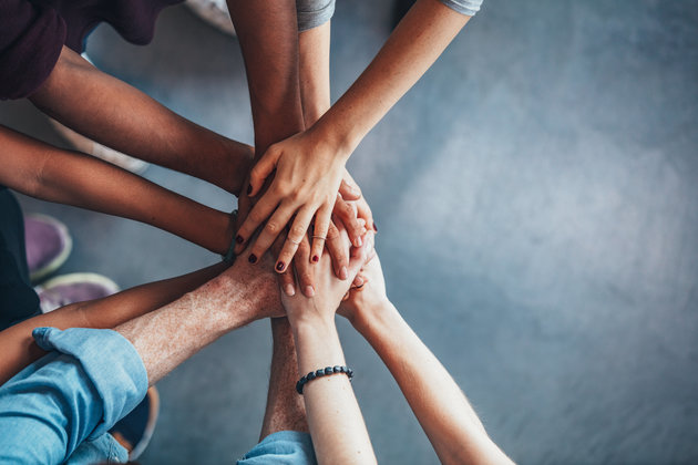 Close up top view of young people putting their hands together. Friends with stack of hands showing