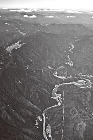 小丸川発電所の全景。山の上にある「上の池」(左上)と、蛇行する川をせき止めた「下の池」の間で、水をくみ上げたり流下させたりする
