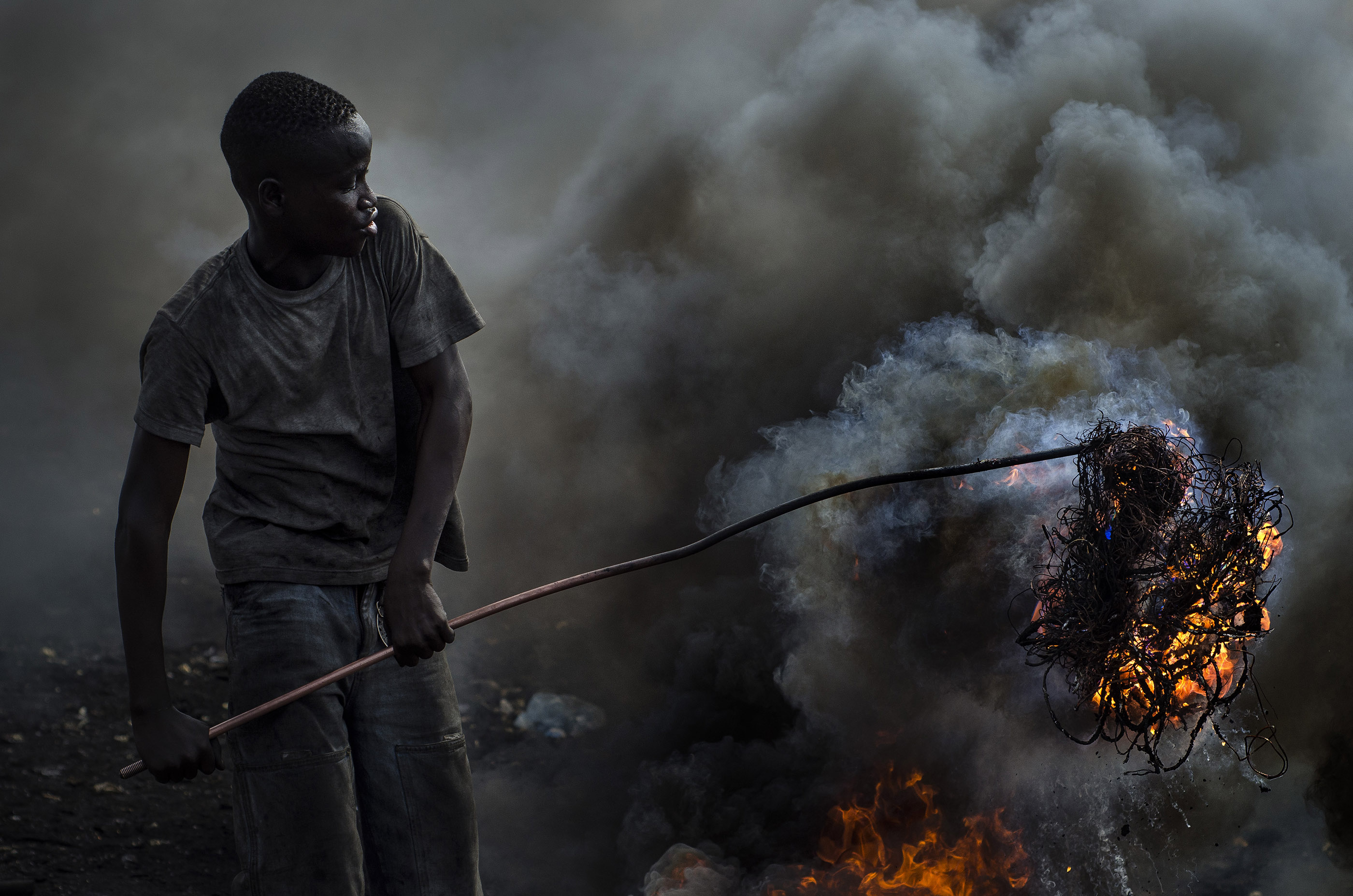 A young man burns cables to retrieve the copper within at an e-waste dump in Agbogbloshie, Ghana.