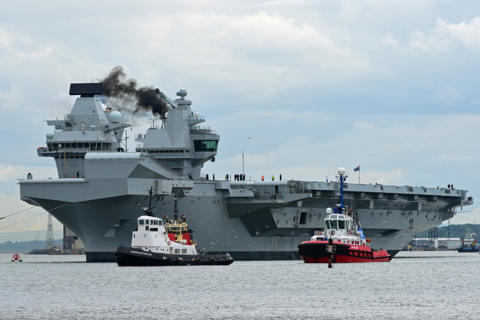 ROSYTH, SCOTLAND - JUNE 26: The aircraft carrier  HMS Queen Elizabeth makes smoke as she leaves Rosyth dockyard to begin sea trials before entering service with the fleet, on June 26, 2017 in Rosyth, Scotland. HMS Queen Elizabeth and her sister ship HMS Prince of Wales, which is still under construction at Rosyth, are the largest warships ever built for the Royal Navy (Photo by Ken Jack - Corbis/Corbis via Getty Images)