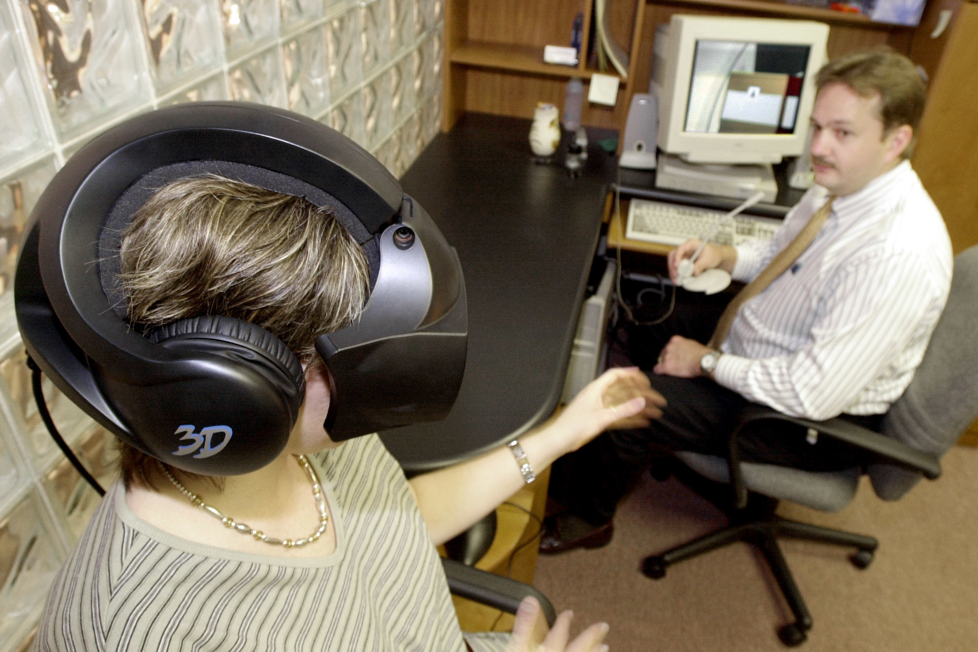 FOR USE WITH FEATURE TITLED VIRTUAL THERAPY -- Esther Begle, left, wears a virtual-reality helmet as she demonstrates a therapy session at Virtually Better Inc. in Atlanta, May 23, 2000, to combat her fear of flying. She reaches toward Ken Graap, CEO of Virtually Better, who uses a computer to control the simulated flight that Begle experiences.  (AP Photo/Ric Feld)