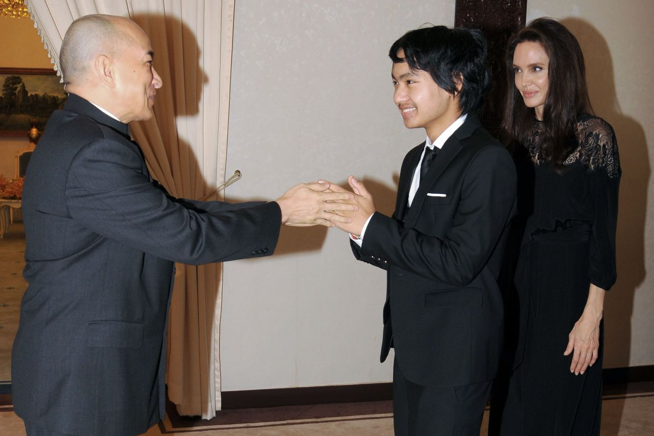 Maddox Jolie-Pitt (C) greets Cambodian King Norodom Sihamoni (L) as Hollywood star Angelina Jolie (R) looks on during an audience at the royal residence in Siem Reap on February 18, 2017. Angelina Jolie will unveil her new film on the horrors of the Khmer Rouge era on February 18 at the ancient Angkor Wat temple complex in Cambodia, a country the star shares a deep affinity with through her adopted son Maddox. / AFP / STR        (Photo credit should read STR/AFP/Getty Images)
