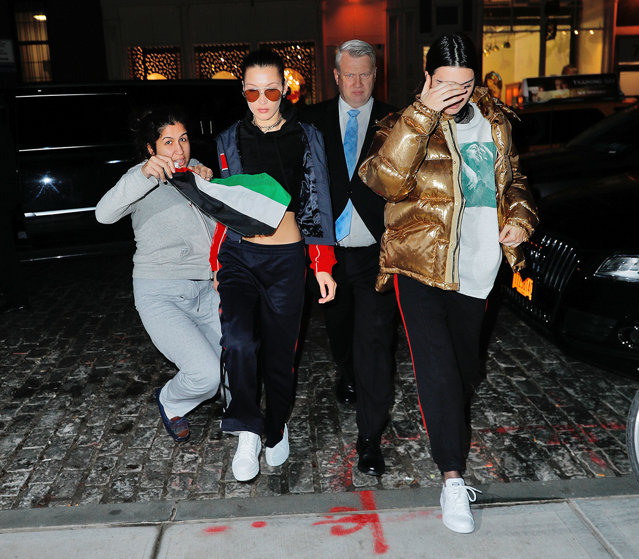 Scary moment as a crazed fan drapes the Palestinian flag across Bella Hadid and Kendall Jenner upon arrival at Gigi's apartment in New York.� The fan was arrested by police moments later <P> Pictured: Bella Hadid, Kendall Jenner <B>Ref: SPL1424695  180117  </B><BR/> Picture by: Jackson Lee / Splash News<BR/> </P><P> <B>Splash News and Pictures</B><BR/> Los Angeles:310-821-2666<BR/> New York:212-619-2666<BR/> London:870-934-2666<BR/> photodesk@splashnews.com<BR/> </P>