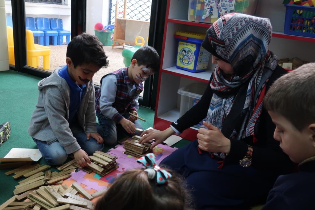 同じく幼稚園で、先生が手話で行う指示に従って一心に積木を並べる園児たち。