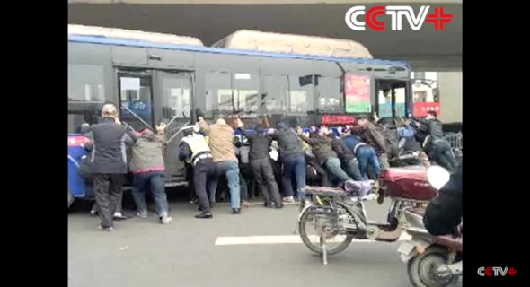 Passengers lift bus off man trapped underneath after accident (video)