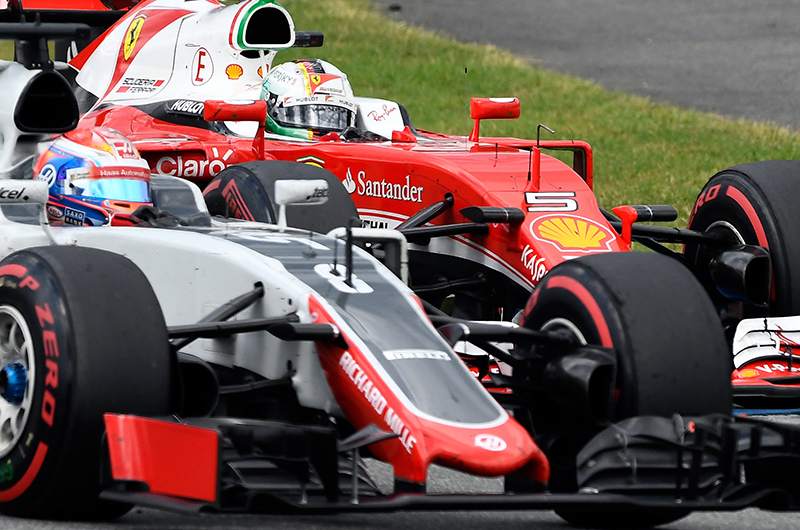 Ferrari driver Sebastian Vettel of Germany, right, takes a curved together with Haas driver Romain Grosjean of France during the German Formula One Grand Prix in Hockenheim, Germany, Sunday, July 31, 2016.