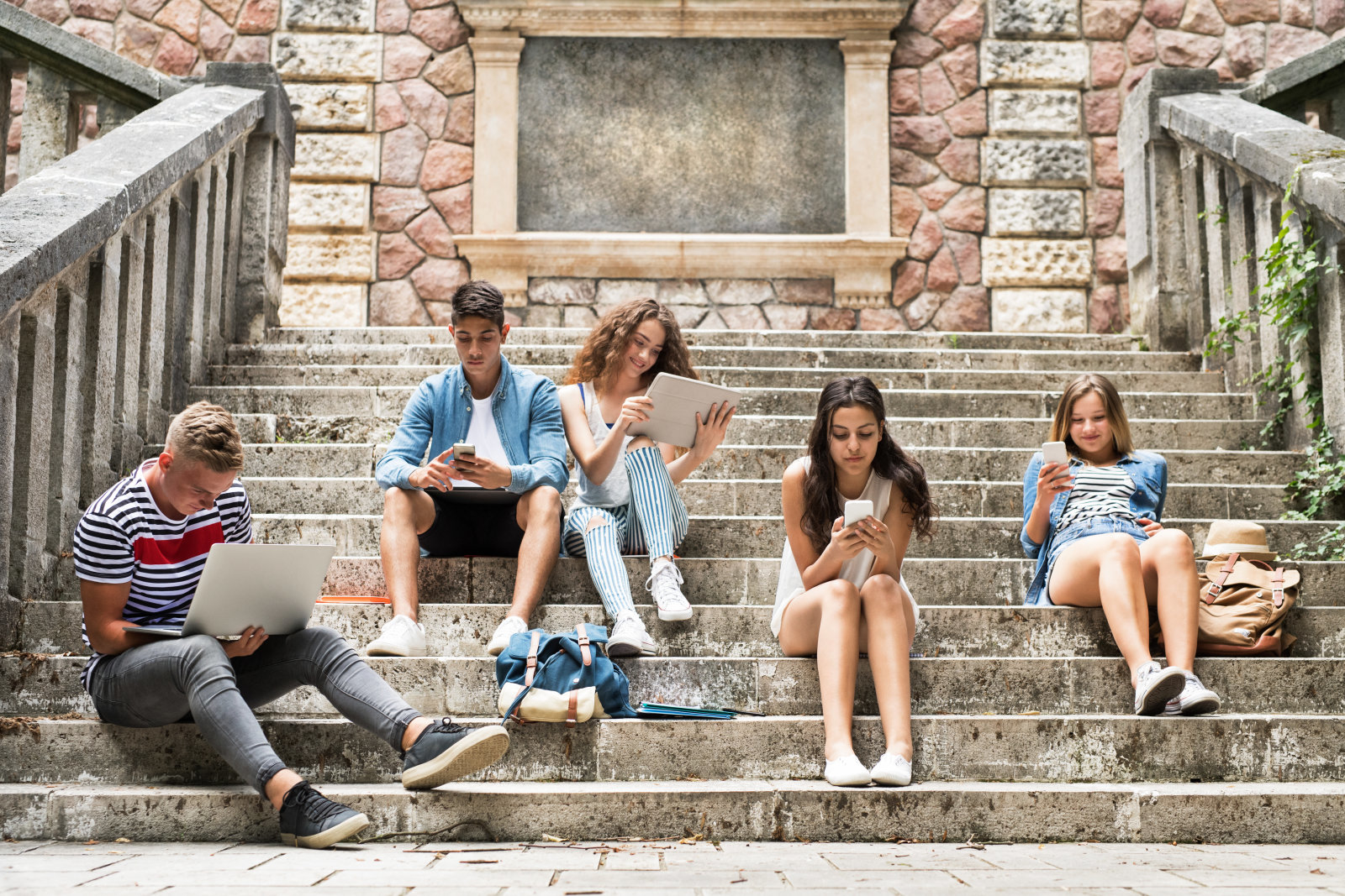 Group of attractive teenage students sitting on stone steps in front of university holding tablet, laptop and smart phones, reading or watching something.