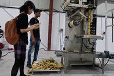 ナッツ販売を企画するテナントが導入したパッキング用の機械。パレスチナのでは生活習慣病予防のため、ナッツの摂取が推奨されている。JICAパレスチナ事務所の平田知美さん(左)がパッキングの出来具合をチェックする