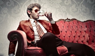 10171766 - young man sitting on a sofa and drinking a glass of