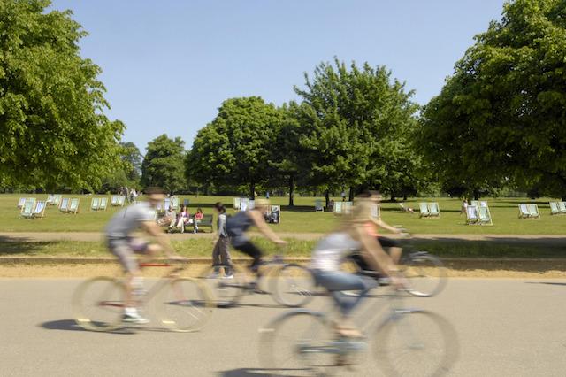 Cyclists enjoy the sun in Hyde Park, London.