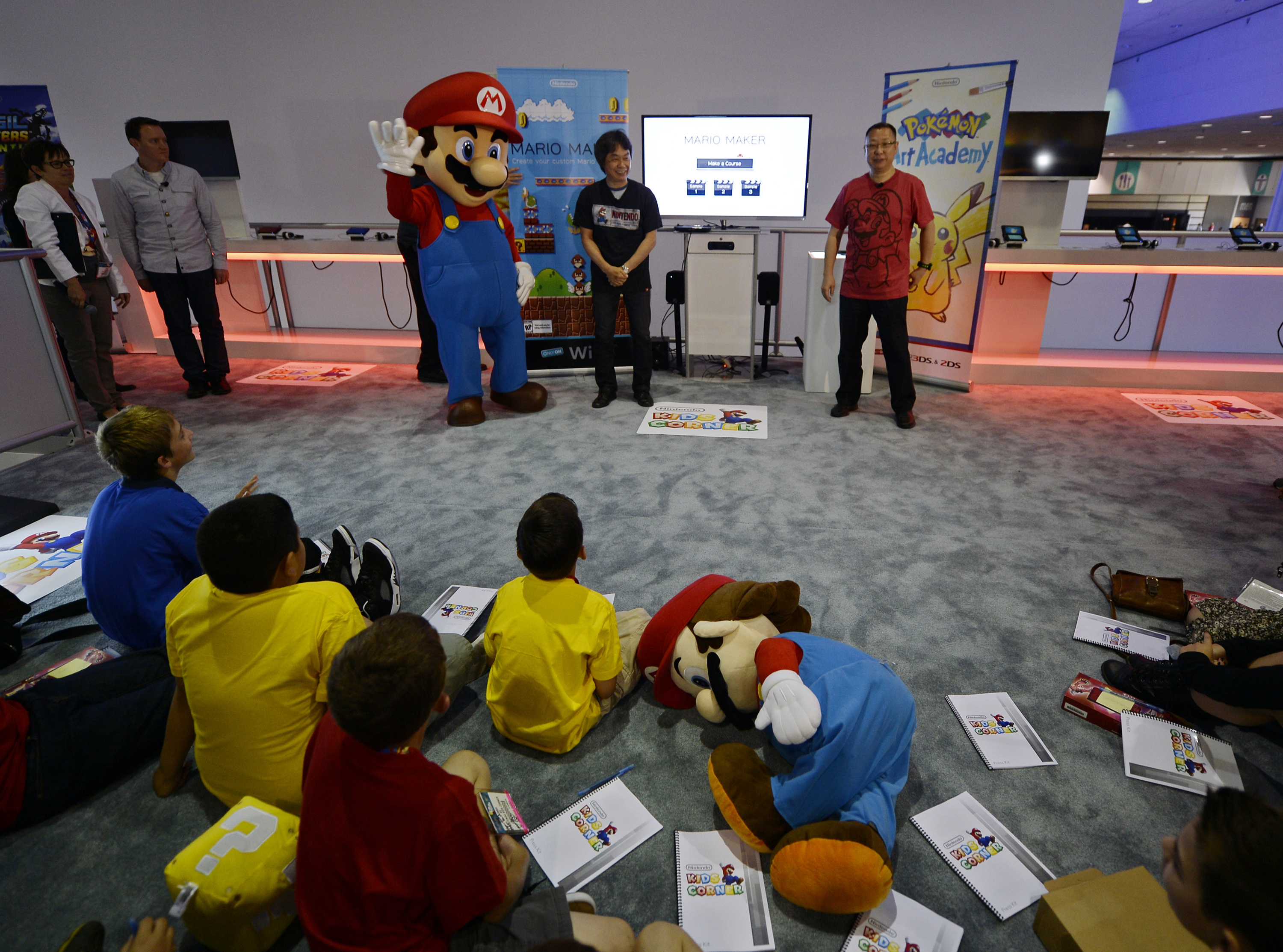 """Shigeru Miyamoto (C), Nintendo's senior managing director and general manager of its Entertainment Analysis and Development division, and Takashi Tezuka (R), executive officer of Nintendo's Entertainment Analysis and Development division, together with Nintendo's character Mario (L), introduce a new game """"Mario Maker"""" while a small group of children look on during a news conference at the 2014 Electronic Entertainment Expo, known as E3, in Los Angeles, California June 11, 2014.  REUTERS/Kevork Djansezian  (UNITED STATES - Tags: SCIENCE TECHNOLOGY SOCIETY BUSINESS TPX IMAGES OF THE DAY)"""