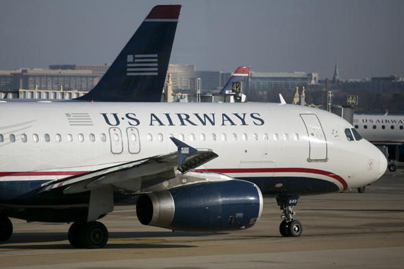 A US Airways Group Inc. airplane taxis at Reagan National Airport in Washington, D.C., U.S., on Thursday, Feb. 14, 2013. US Airways Group Inc., spurned in three prior merger attempts, will combine with bankrupt AMR Corp.'s American Airlines in an $11 billion deal to create the world's largest carrier. Photographer: Andrew Harrer/Bloomberg via Getty Images