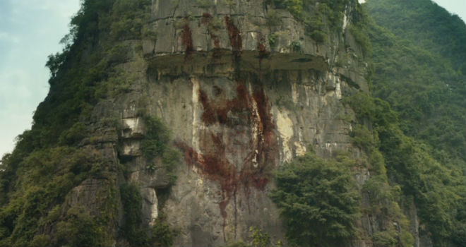 A giant, bloody handprint adorns the cliffside of a mountain on SKULL ISLAND