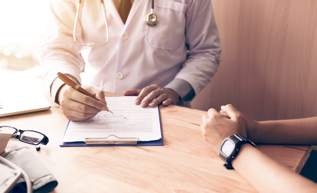 Doctor hand holding pen writing patient history list on note pad and talking to the patient about medication...