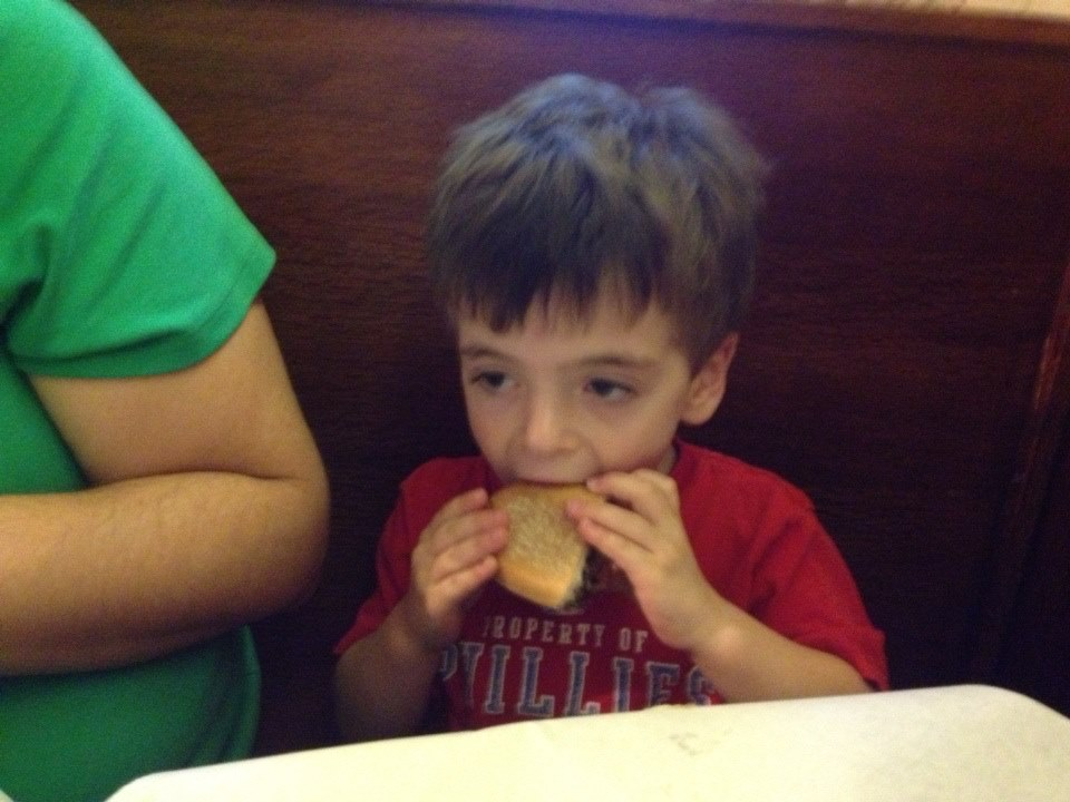 The author's son takes a bite of his first cheesesteak, at Joe's Steak and Soda Shop in 2013