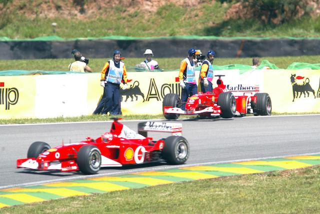The new Ferrari F2002 of Michael Schumacher passes team mate Rubens Barrichello's stricken old Ferrari F2001 out on the circuit as Schumacher decision to try out the new car seems to have worked