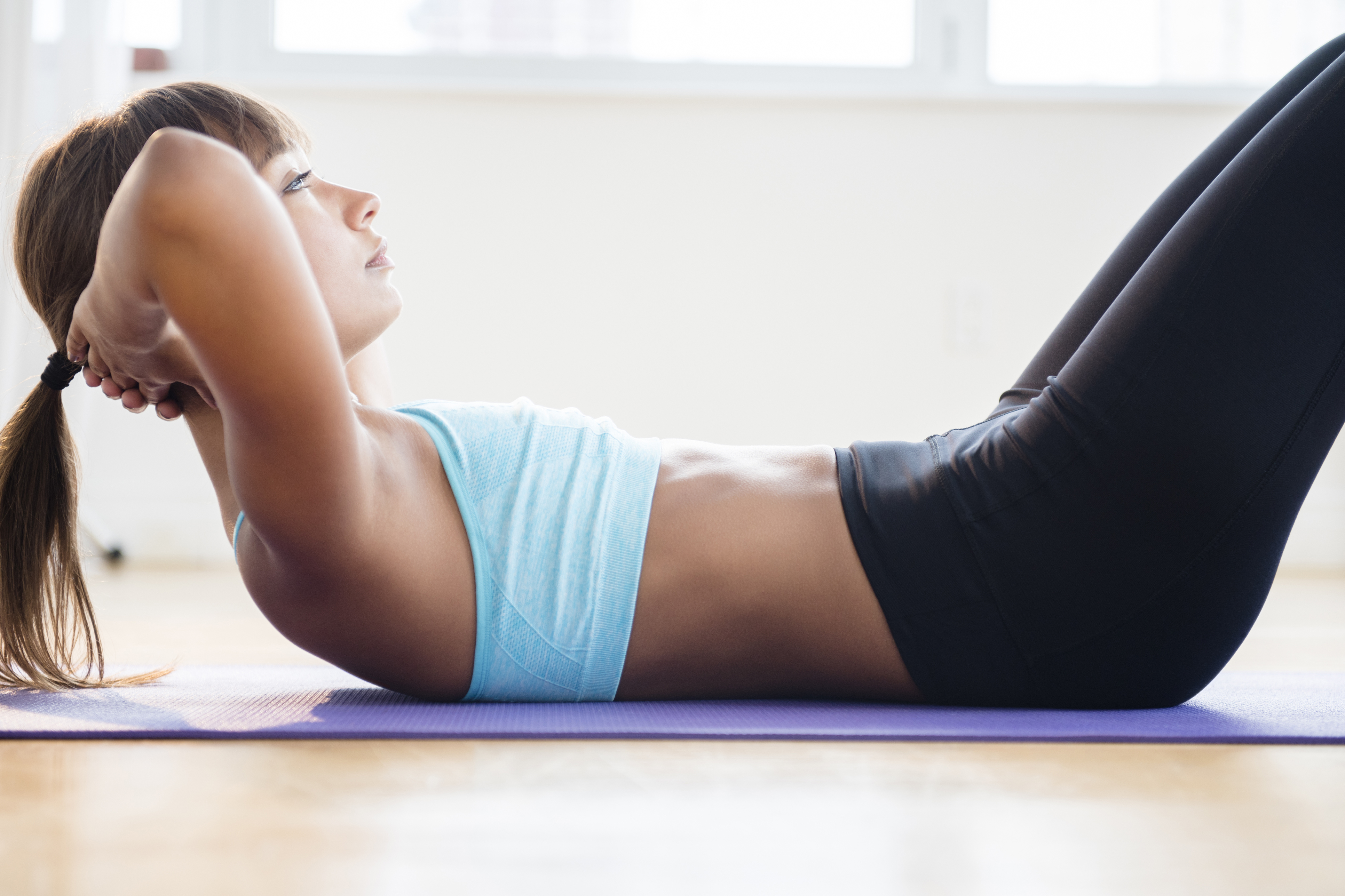 Mixed race woman doing sit-ups on yoga mat